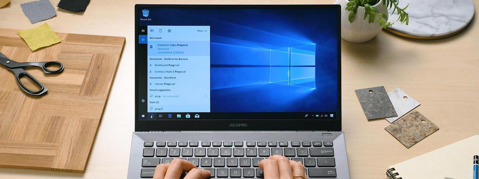 Ноутбук на столе с Поиском в корпоративной среде на экране