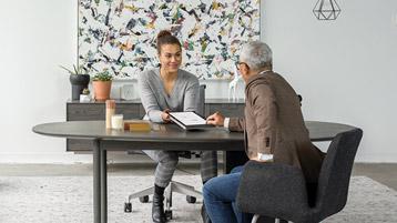Женщина, показывающая через стол планшет мужчине
