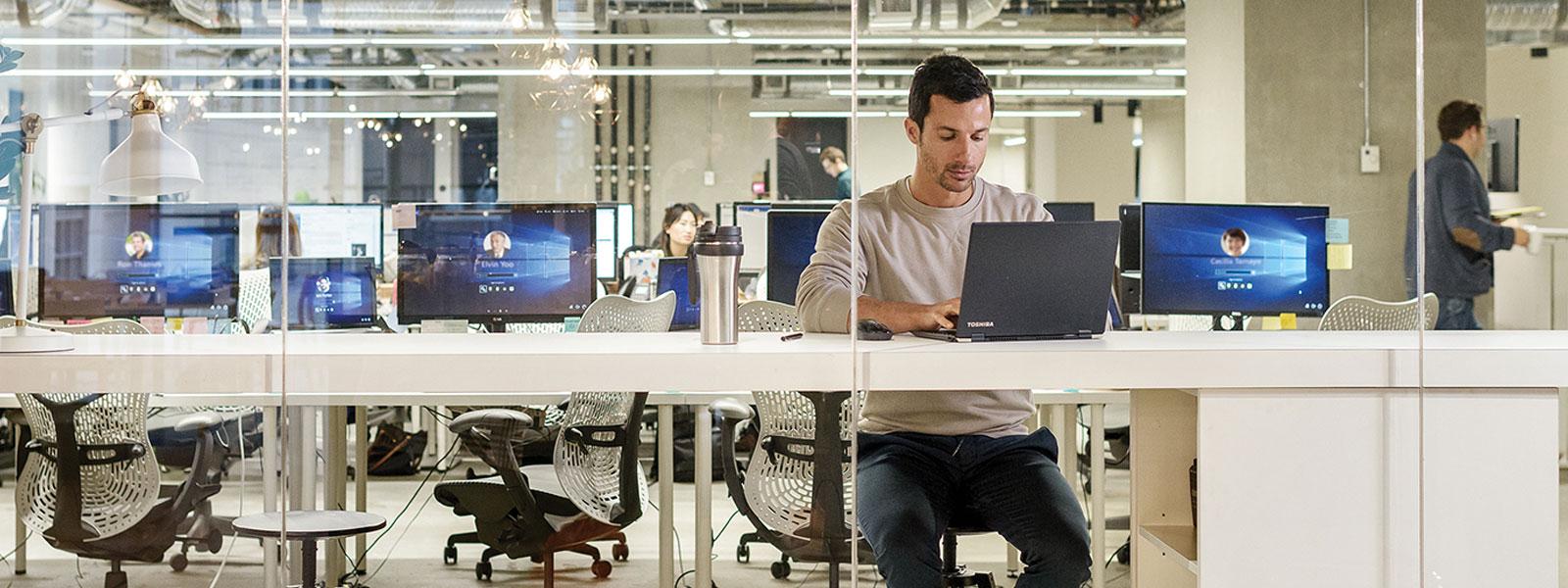 Мужчина, использующий ноутбук в офисе открытого типа