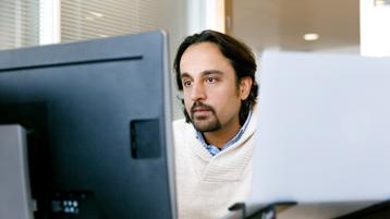 Мужчина за столом смотрит в монитор