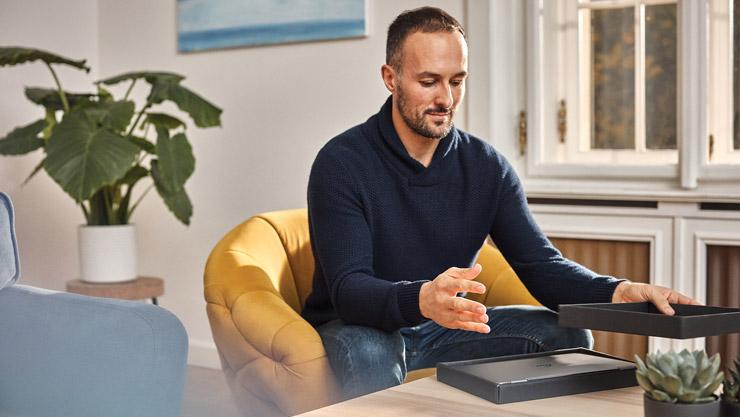 Мужчина открывает коробку с новым ноутбуком