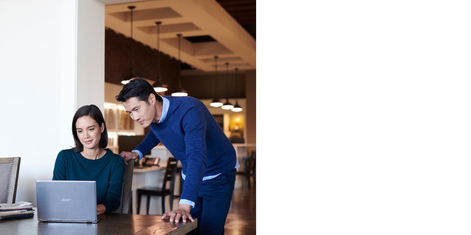 Мужчина смотрит в ноутбук через плечо женщины