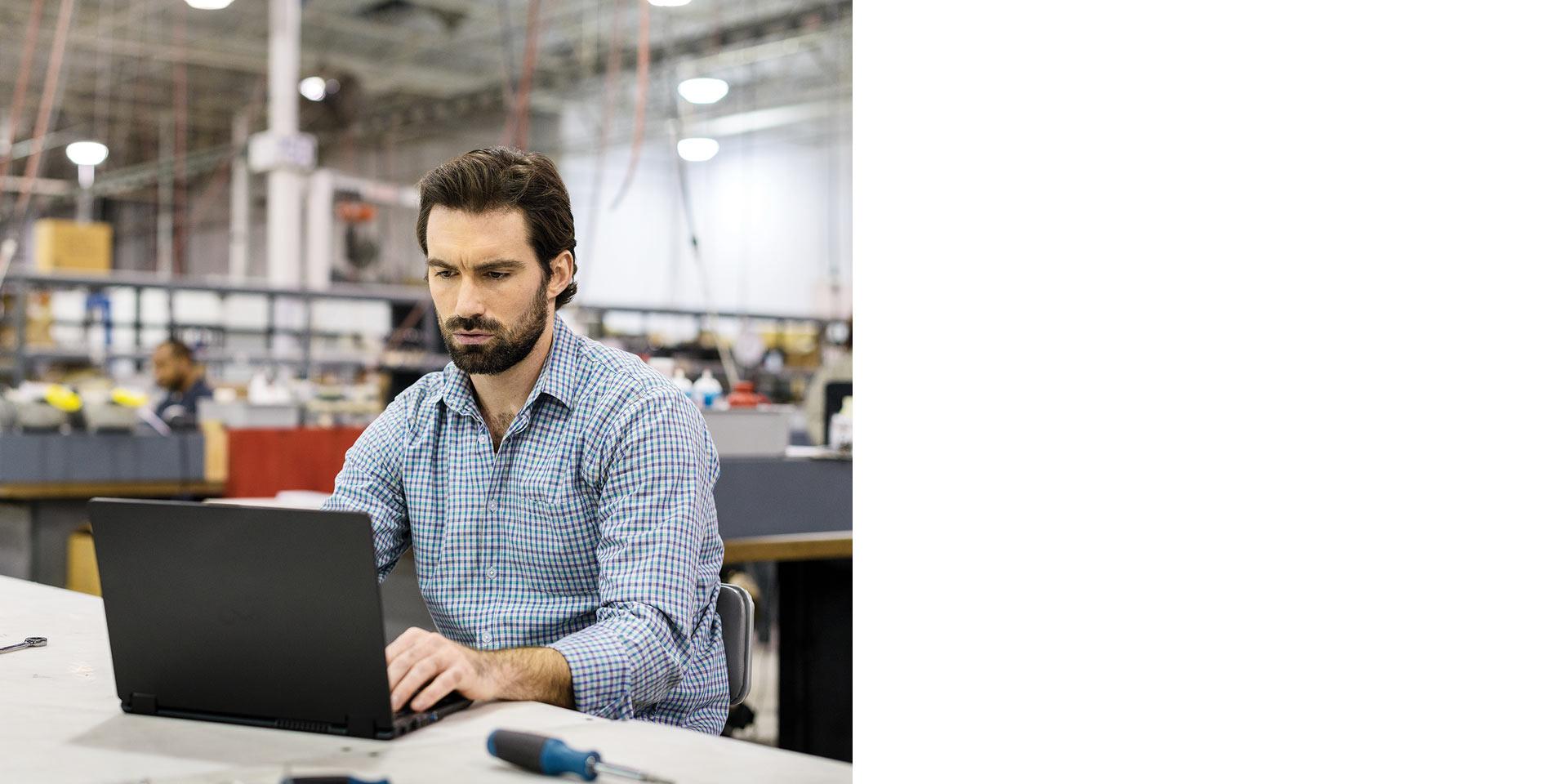 Мужчина пользуется ноутбуком на заводе