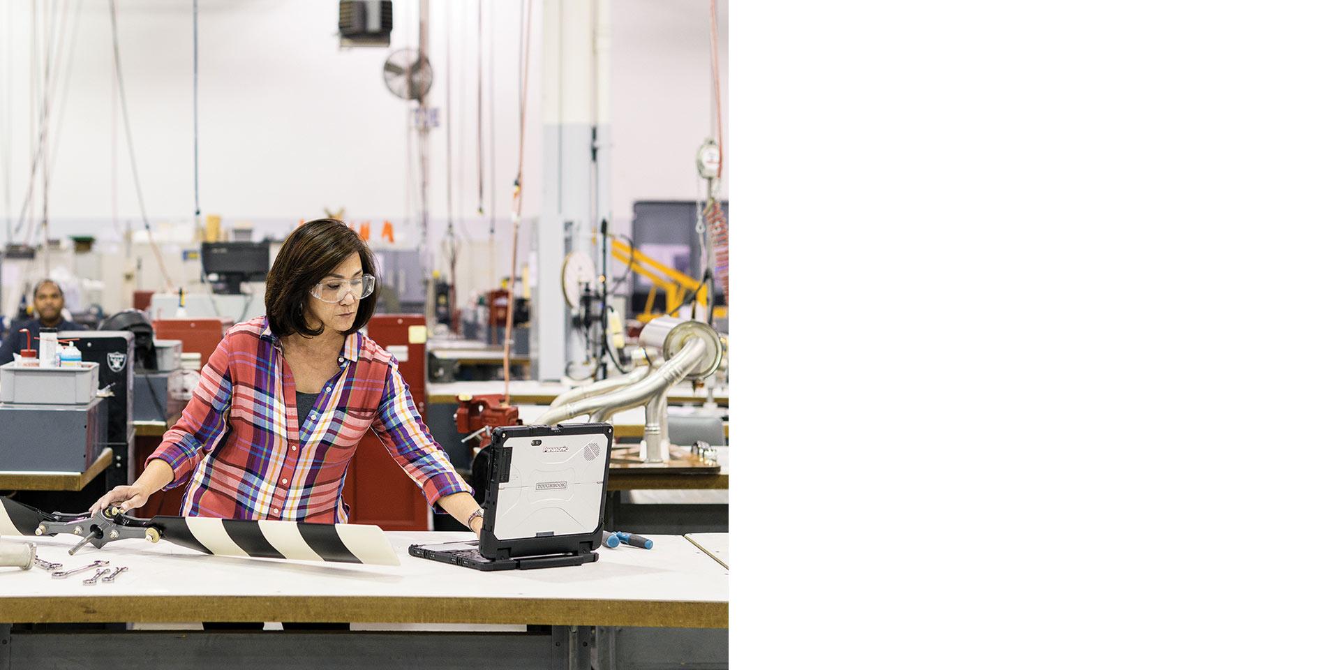 Женщина пользуется ноутбуком на заводе