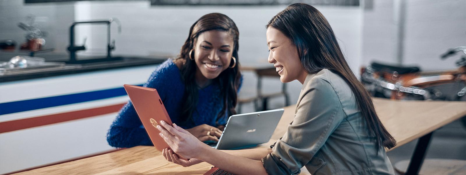 две женщины делятся содержимым на экране ноутбука 2-в-1