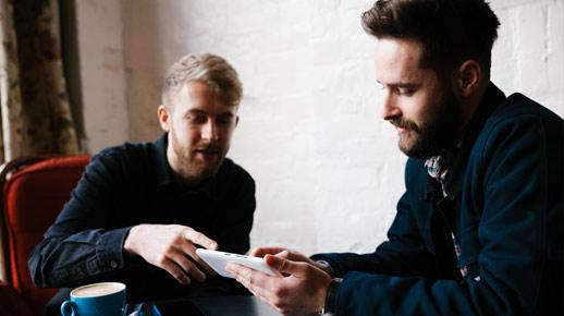 Двое мужчин смотрят на телефон