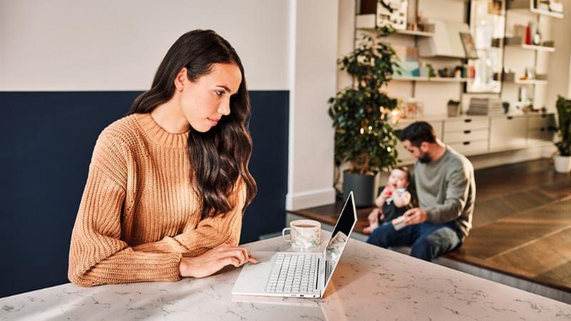 Женщина работает с ноутбуком дома