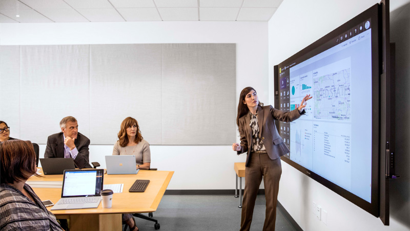 Женщина проводит презентацию на совещании перед Surface Hub