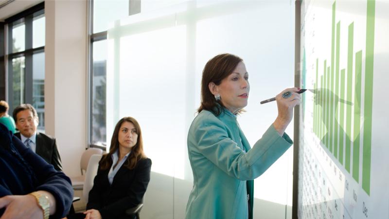 Женщина, работающая с Surface Hub перед аудиторией