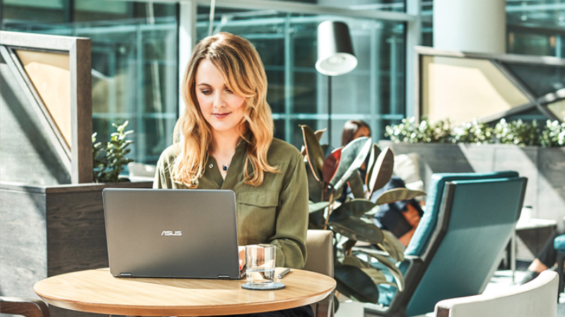 Женщина работает с ноутбуком в кафе