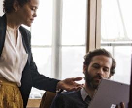 Мужчина и женщины что-то обсуждают перед планшетом