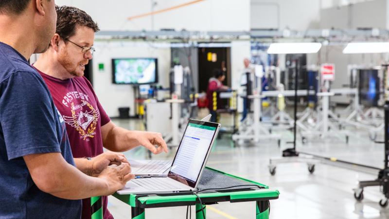 Двое мужчин, работающие с ноутбуком в производственном помещении