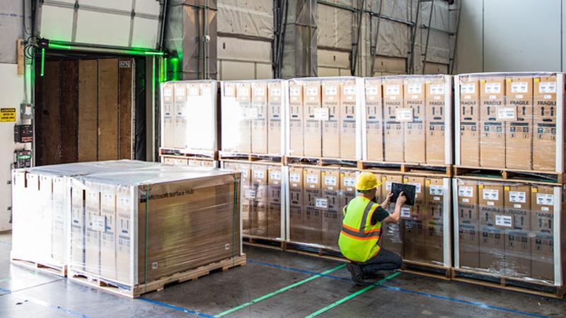 Мужчина в производственном помещении перед большими ящиками