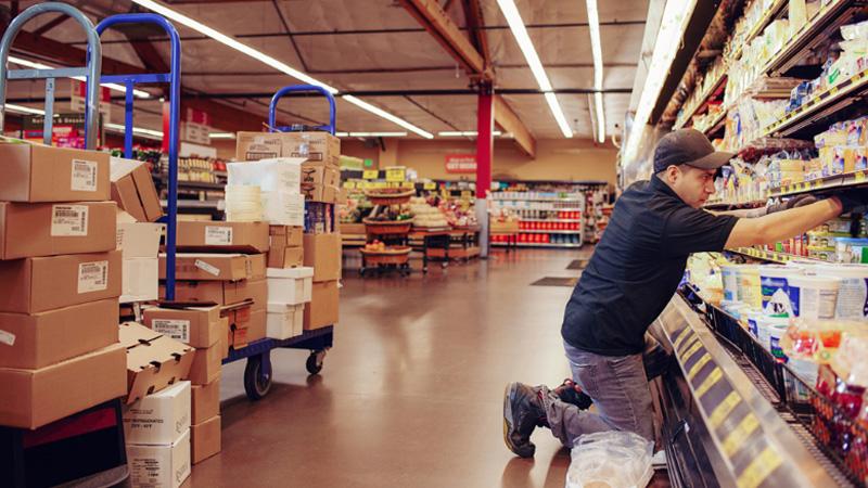 Мужчина, обслуживающий полки в супермаркете