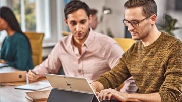 Двое мужчин работают с компьютером