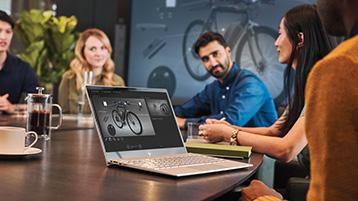 Ноутбук на столе, вокруг люди на совещании