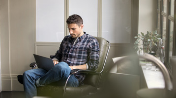 Мужчина, сидящий дома в кресле и работающий с ноутбуком