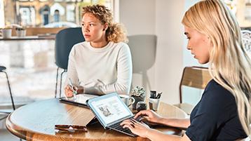 Две женщины, сидящие за столом и работающие с ноутбуком