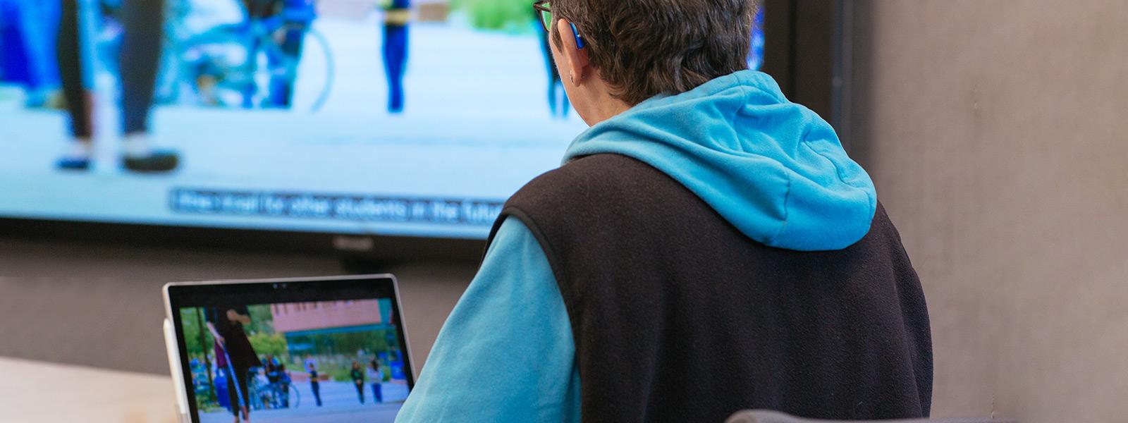 Žena s načúvacím prístrojom sleduje videoprezentáciu s titulkami