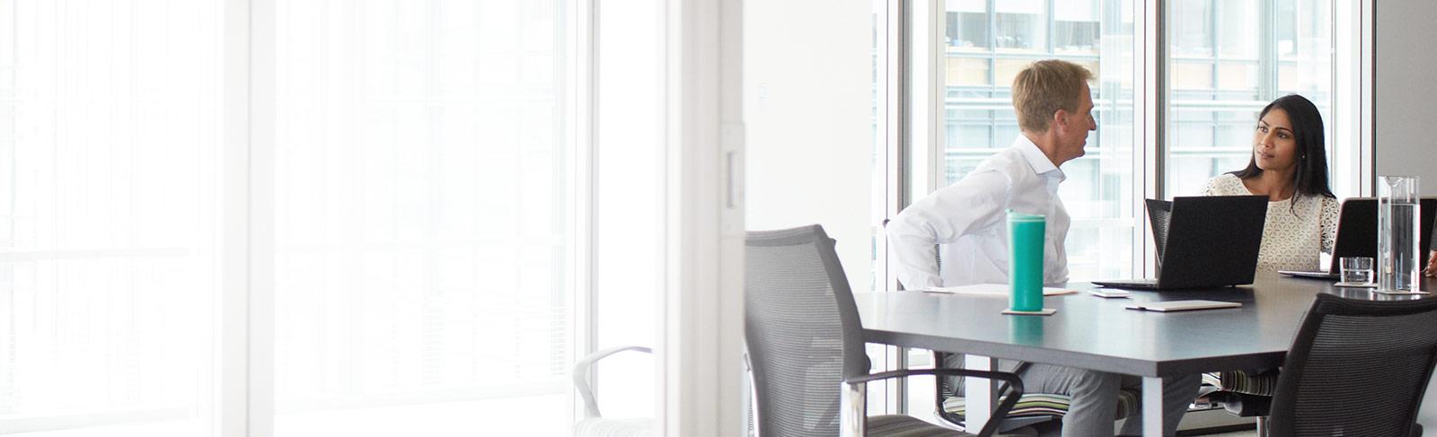 Dvaja pracovníci s prenosnými počítačmi v konferenčnej miestnosti používajúci Office 365 Enterprise E3.