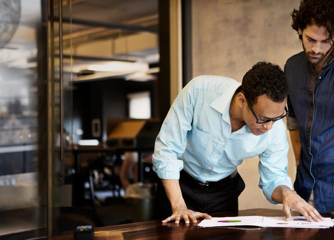 Dvaja muži, ktorí pracujú vkancelárii apoužívajú Office 365 Enterprise E4.