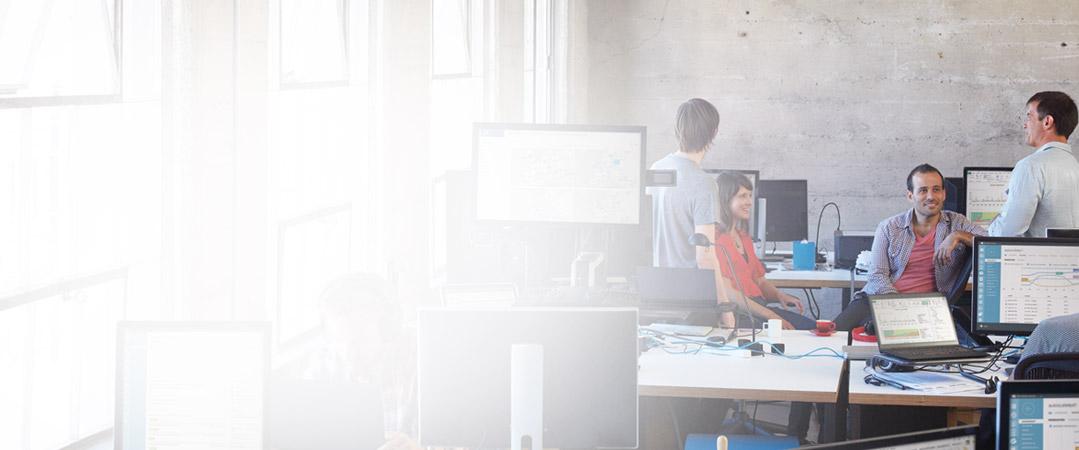 Päť ľudí v kancelárii pracujúcich na stolných počítačoch, na ktorých sú spustené služby Office 365.