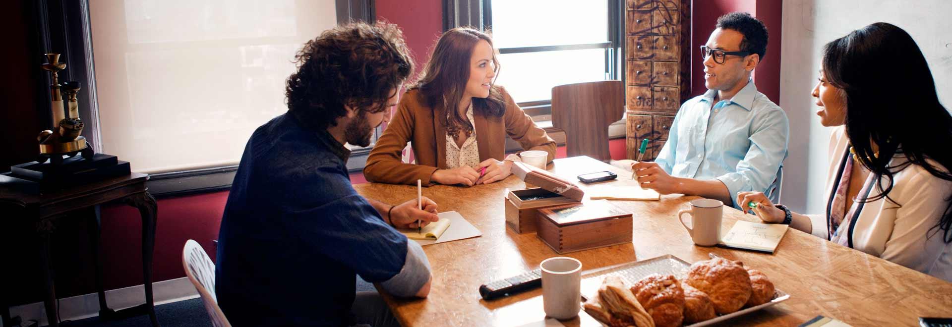 Štyria ľudia pracujúci v kancelárii a používajúci Office 365 Enterprise E3.