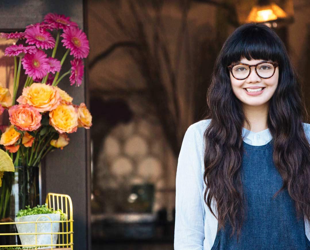 Mlada ženska z očali, ki se smehlja, stoji na prostem ob vazah z rožami.