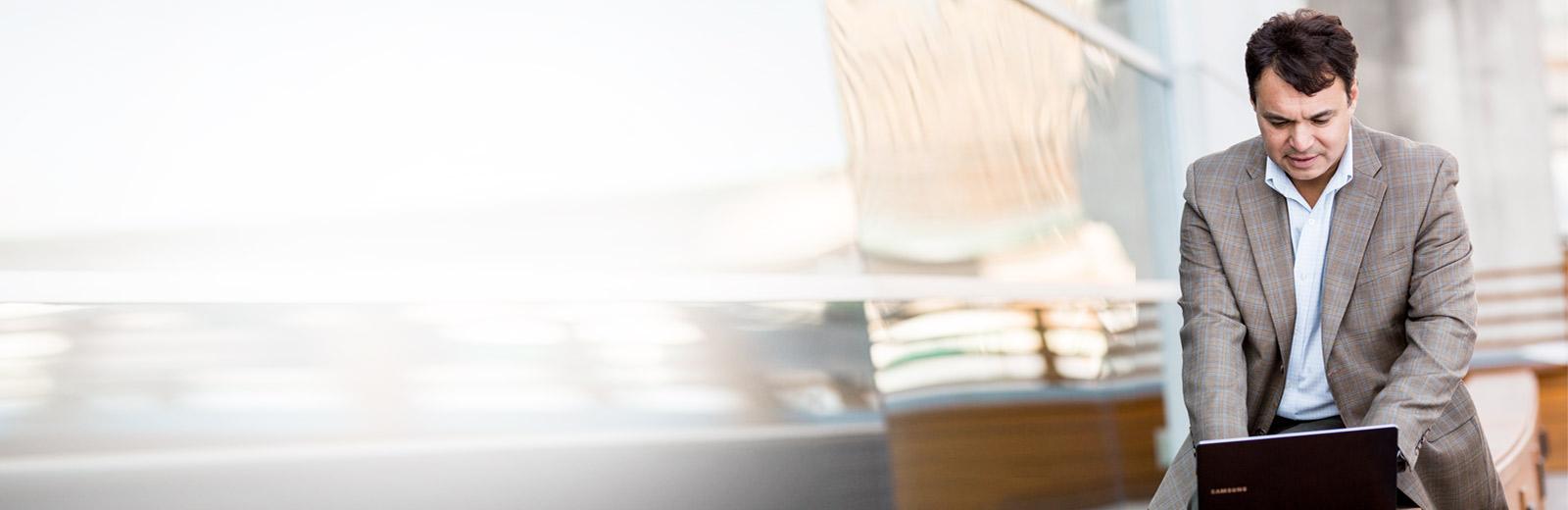 Moški za delo v prenosniku uporablja poslovno e-pošto v storitvi Exchange Online.