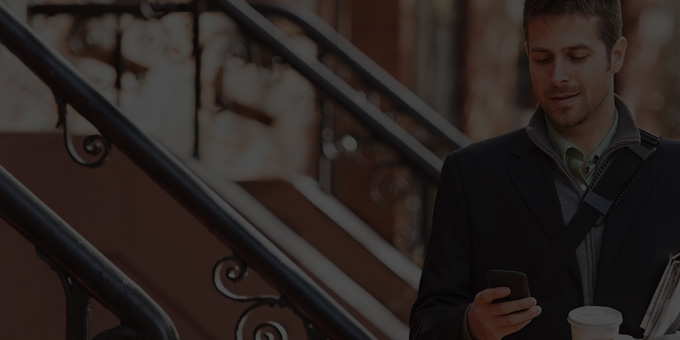 Moški drži v rokah pametni telefon in uporablja Office 365 Enterprise E1.
