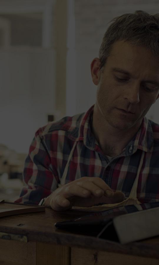 Moški v delavnici, ki uporablja Office 365 Business v tabličnem računalniku.