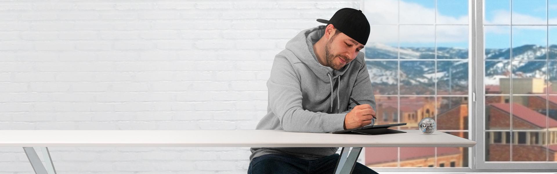 Nasmejan moški, ki sedi za mizo s prenosnikom Surface.