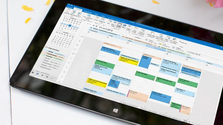 Tablični računalnik s prikazanim odprtim koledarjem v programu Outlook 2016 in vremenom za izbrani dan.