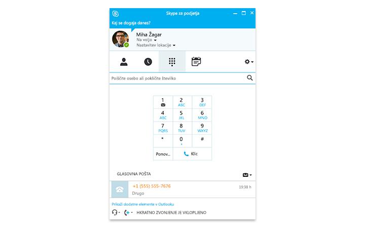 Oseba, ki vnaša podatke v tablični računalnik Surface, na zaslonu pa je prikazano spletno srečanje v Skypu za podjetja