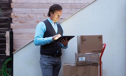 Moški v bližini naložene embalaže za delo uporablja svoj tablični računalnik in Office Professional Plus 2013