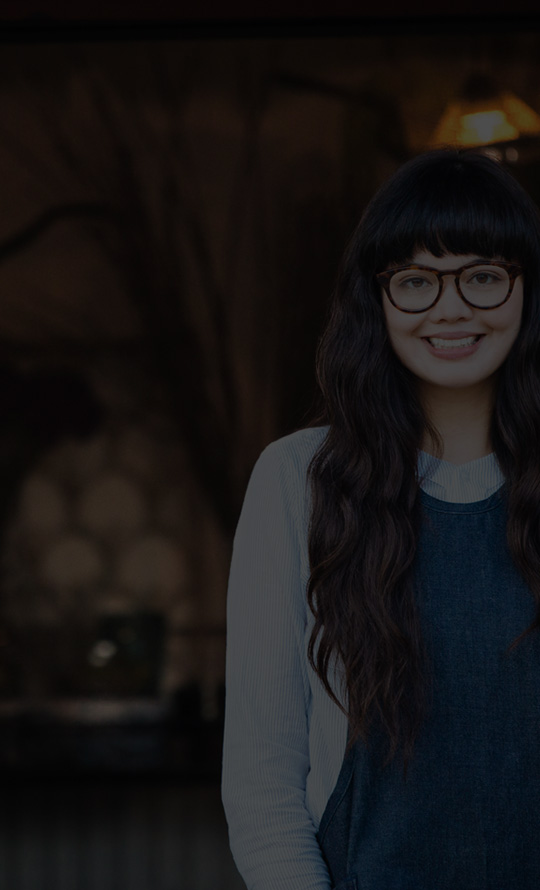 Nasmejana devojka sa naočarima stoji napolju pored posuda sa isečenim cvećem.