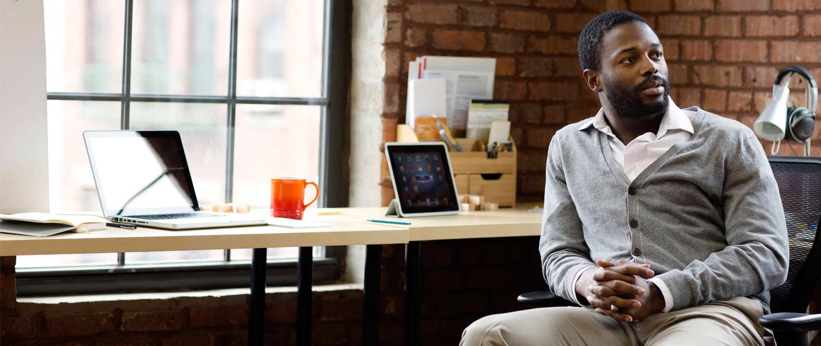 Muškarac koji sedi za stolom sa tabletom i laptopom i koristi Office 365 Business Premium.