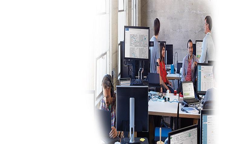 Sex personer arbetar vid sina skrivbord på ett kontor, och använder Office 365.