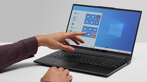 En hand pekar på startskärmen på en bärbar Windows10-dator