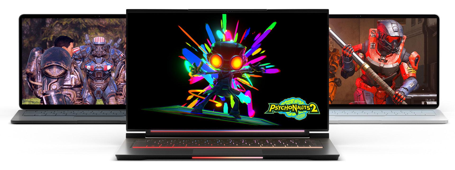 Tre bärbara datorer med datorspel som visas på skärmen