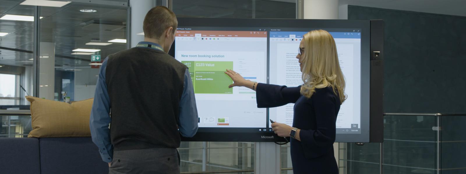 En kvinna och en man står framför en hubb med PowerPoint och Word öppna på skärmen