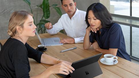 Tre kollegor vid ett bord har ett möte medan de konsulterar skärmen på en Surface Pro 6 i matt svart