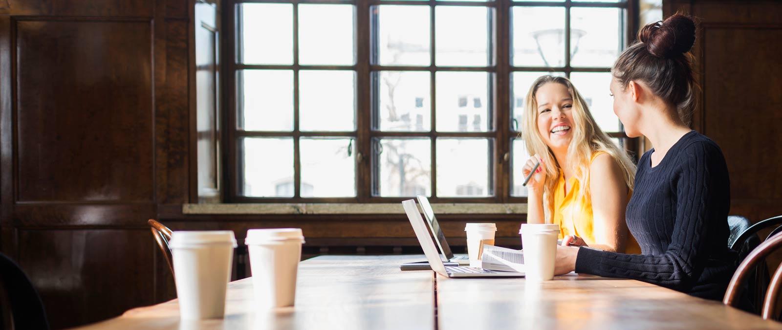 Två kvinnor sitter vid ett bord och använder Office 365 ProPlus på sina bärbara datorer.