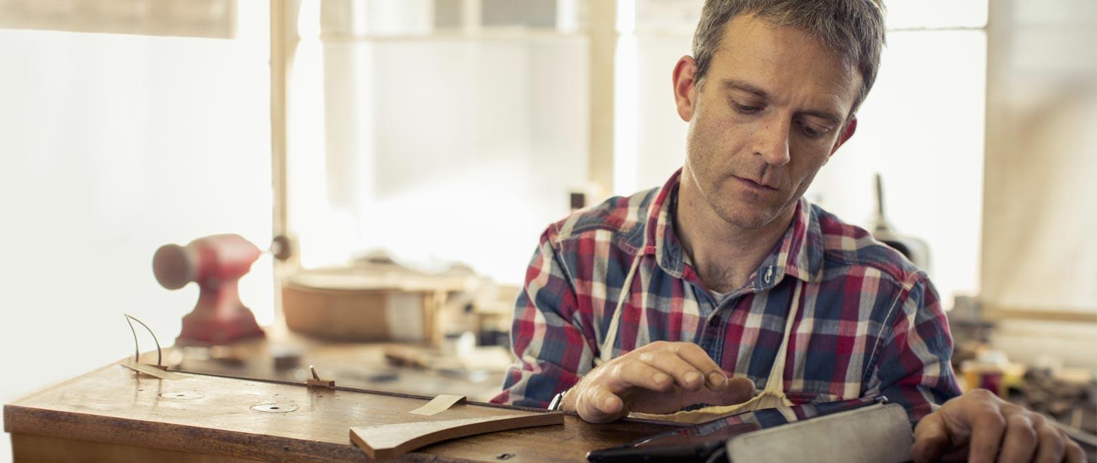 En man i en verkstad som använder Office 365 Business på en surfplatta.