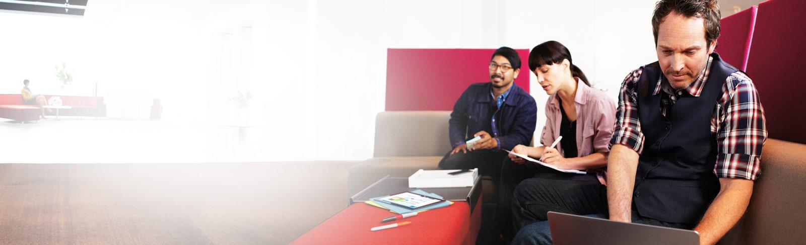 Tre personer med en bärbar dator och anteckningsböcker. De använder SharePoint Online.