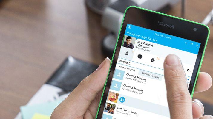 En hand som håller i en mobil enhet där Skype används för att ringa ett samtal