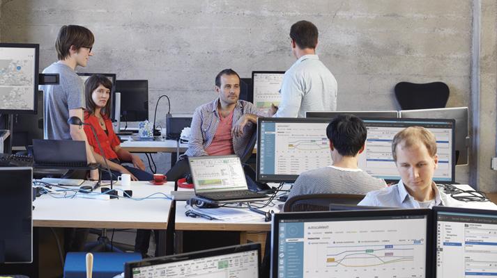Medarbetare som sitter och står runt bord i ett öppet kontorslandskap.