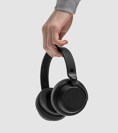 En man håller i Surface Headphones 2