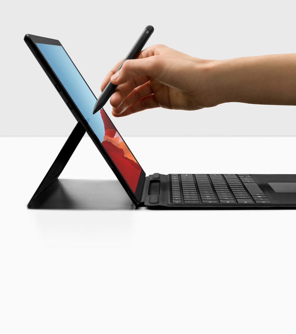 En hand skriver med Surface Slim Pen på en Surface Pro X