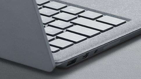 Sidovy av en platinafärgad Surface Laptop som framhäver gångjärn och Alcantara-tangentbordet.